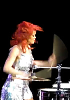 You may have seen Rihanna behind a drum kit in the video for Rude Boy, and she also had private drumming lessons from Travis Barker. Now Rihanna is blazing the drums on stage to the Sheila E. song The Glamorous Life.